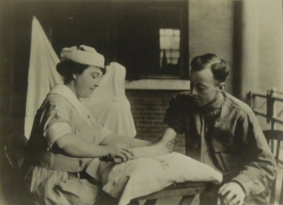 Two seated people, one in medical clothing and the other in army clothing, facing each other. The nurse is massaging the patient's arm.