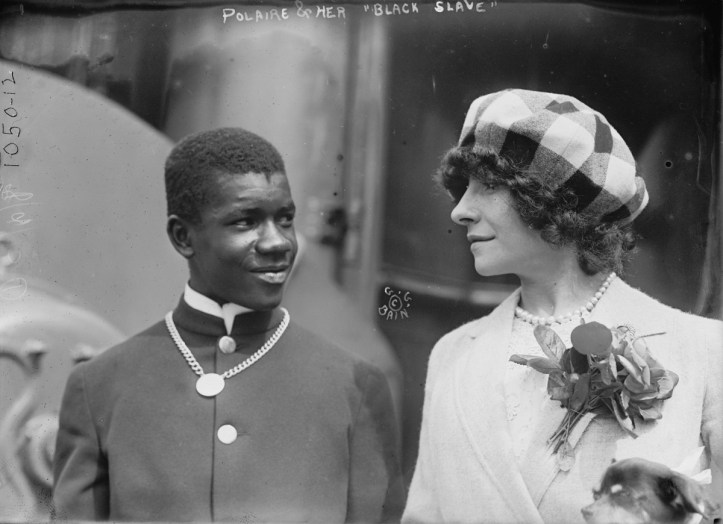 A dark-skinned man in a suit wearing a necklace next to a light-skinned woman with curly hair wearing a hat.