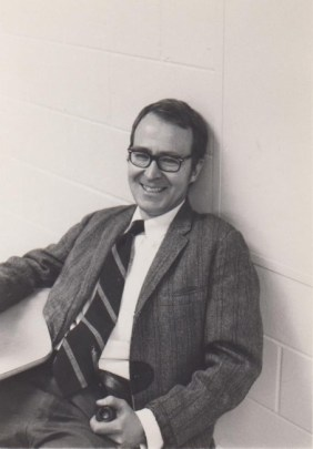 Black and white photo of a 40-something white man sitting in a chair and leaning against a white cement block wall, laughing. He wears black-rimmed glasses, a gray suit with a striped tied and white button-up shirt.