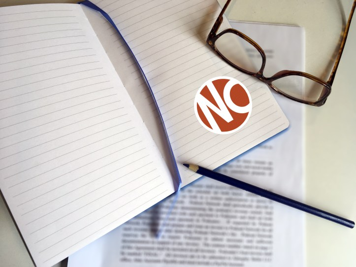 Photo of an open notebook with the Nursing Clio logo, a pair of glasses, and a blue pen