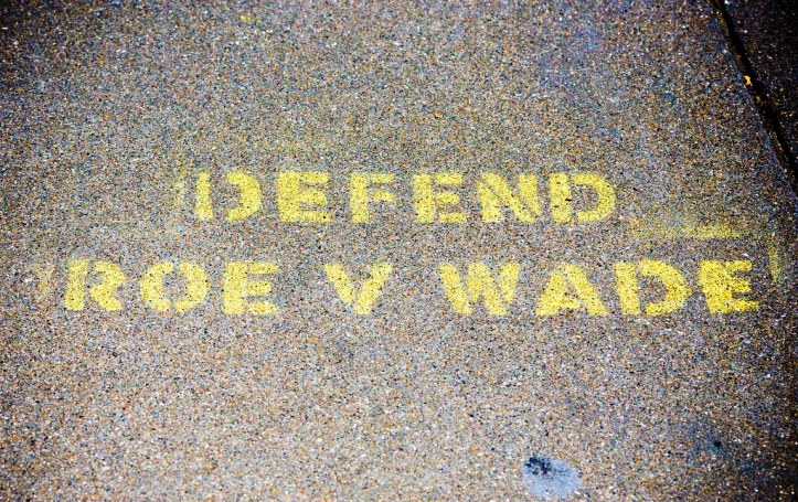 Spraypainted sidewalk with the text: Defend Roe v Wade.