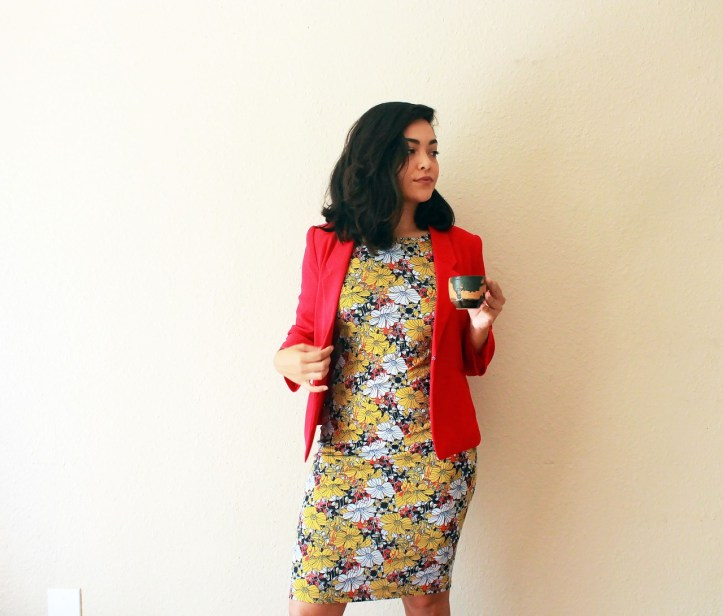 White woman in a yellow and white print dress with a red blazer