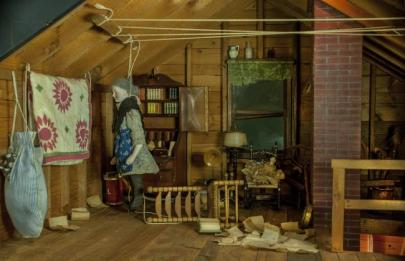 photo of a diorama showing a woman standing in the corner of the room (well, she's actually a doll - it's a diorama) with furniture knocked over