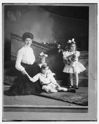 black and white photo probably early 1900s of a woman kneeling with three under-10 children arranged around her