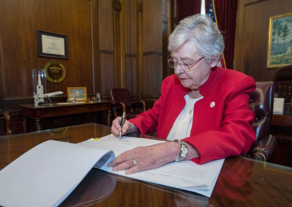 Old white lady in a red blazer signs a document with a pen at a big brown desk