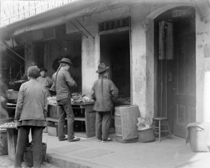 Black and white photo of an exterior fish market stall. Two men with long tight braids and loose cotton shirt and pants stand before a table of fish. Another man walks by in the corner of the frame