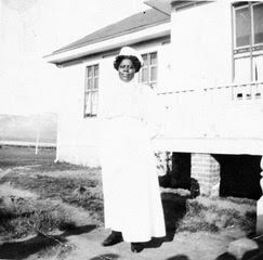 Alice Barnett, with dark brown skin and black hair snug under a nurses hat, stands in a long white dress - her nurses uniform - in front of a white clapboard building, the Indian School.