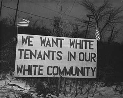 Big billboard-sized sign that states in block letters WE WANT WHITE TENANTS IN OUR WHITE COMMUNITY. There are two American flags, one at each corner of the sign.