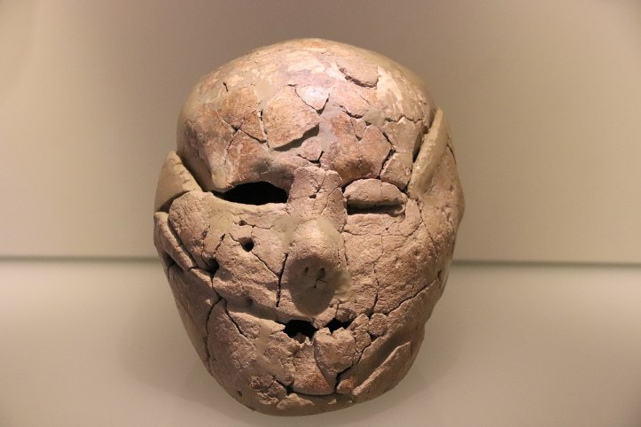 a cracked reddish tan plaster rendering of a face. The right eye seems to be filled with clay like a closed eyelid, the left is open, the mouth is just a few jagged holes, and there are two large holes in the left cheekbone