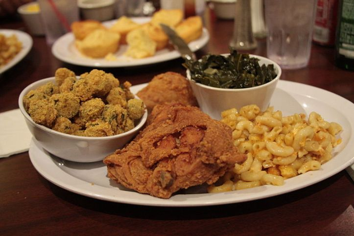 A white platter with friend okra, fried chicken, mac and cheese, and collard greens