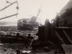 Black and white photo of a large 1-masted ship beached in a harbor that is filled with debris of what looks like a burned out boardwalk and dead ships