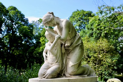 Statue of a woman kneeling and hunched over, hiding her face, clutching a child.