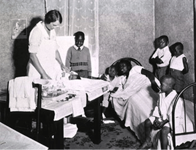 A woman (probably pregnant) is laying in a bed; her five children stand or sit around her on the bed or ear the bed, and another woman in a white apron stands at a table wrapping a new baby in a blanket