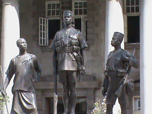Bronze statues of three Kenyan men in military uniform, one standing straight to attention in the center, two others look up at him.