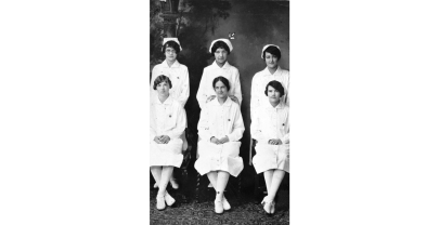 Six young women, including Susie Walking Bear, sit posed for a class photo, three standing in the back, three sitting on chairs int he front, all in white nursing uniforms