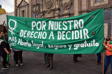 Demonstrators hold a large green banner with write lettering in Spanish.