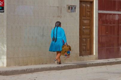 A Bolivian woman wearing long braids walks down a street in Tupiza.