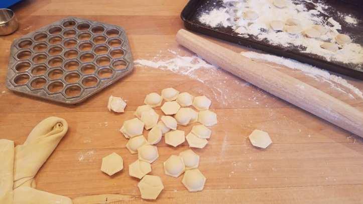 Small Polish dumplings, a rolling pin, and a metal dumpling mold litter a wooden surface.