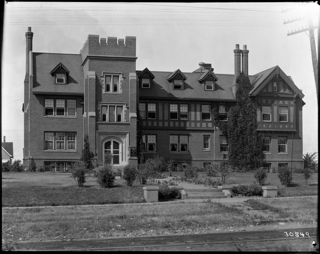 Black and white photo of large brick building with mock Tudor features.