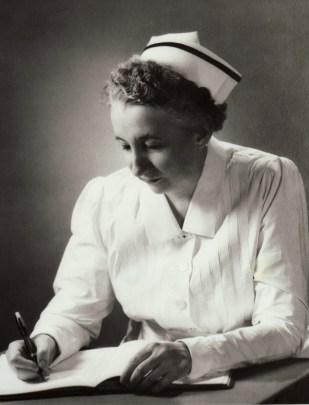 An older woman in a nurse's uniform writes in a notebook. The photograph is black and white and lit as if taken in a photographic studio