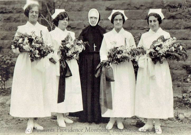 A photograph of a nun in a habit standing in the middle of four women in white nurses uniforms. The nurses hold bouquets of flowers.