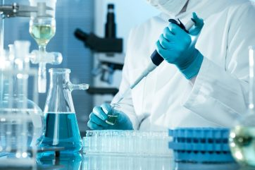 A scientist in white lab coat and gloves inject liquid into a vial in a lab setting.