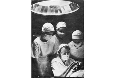 Several women in scrubs and wearing face masks crowd around another woman who appears to be administering anesthetic
