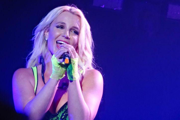Britney Spears, lit by a spotlight, sings into a microphone. She wears neon green fingerless gloves.