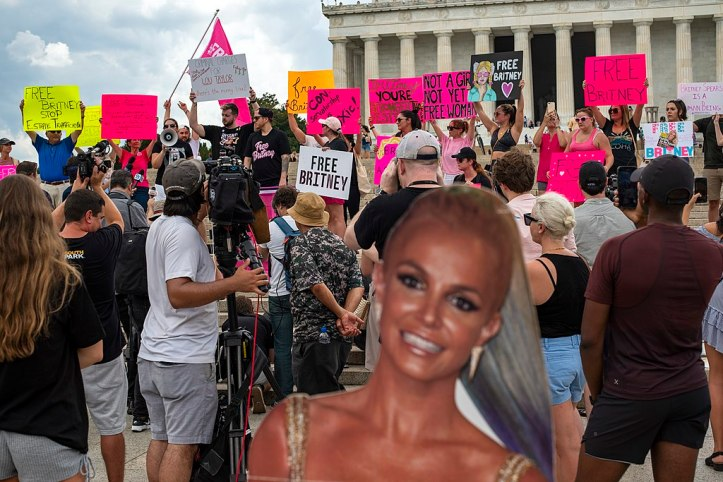 A crowd of Britney Spears supporters hold up signs for the media in front of the Lincoln Memorial. A cardboard Britney is in the foreground.