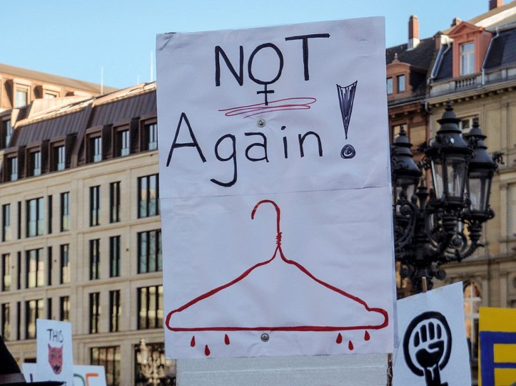 """A poster features a bloodied coat hanger and the words """"Not again!"""""""