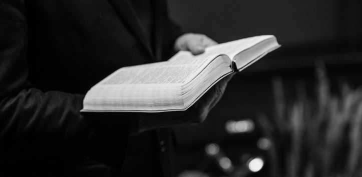 Black and white photo of a man's hands holding a Bible.