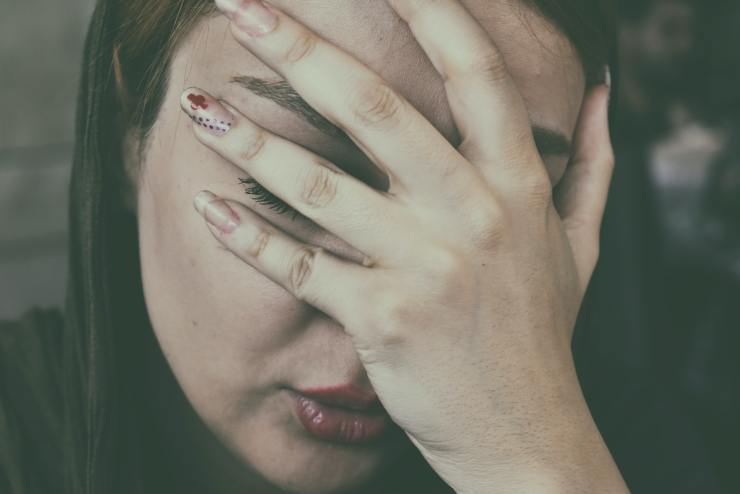 This is a picture of a woman covering her face because she is so upset. Nurtured Well helps women with anxiety in Towson, MD.