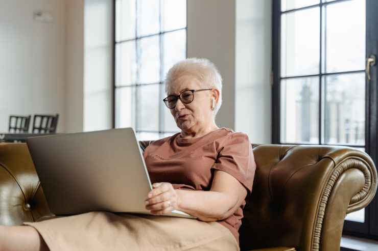 An older woman sitting on a couch.  She is seeing her Psych NP to manage her mood from her home in Maryland.