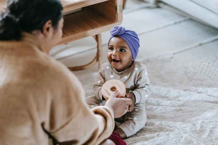 mother giving toy to african american baby.  You can enjoy motherhood like this with practicing  mindfulness.