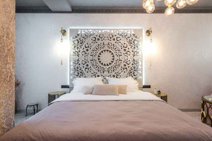 bedroom interior with carved panel between shiny lamps