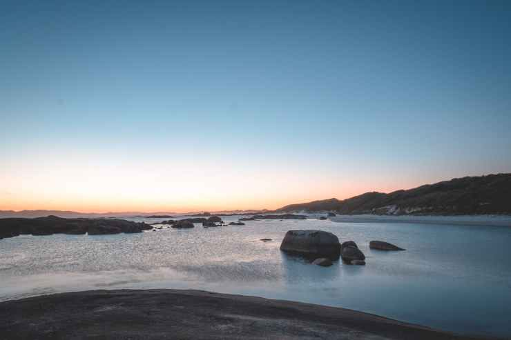 peaceful rocky sea under cloudless sundown sky.  This represents mindfulness.