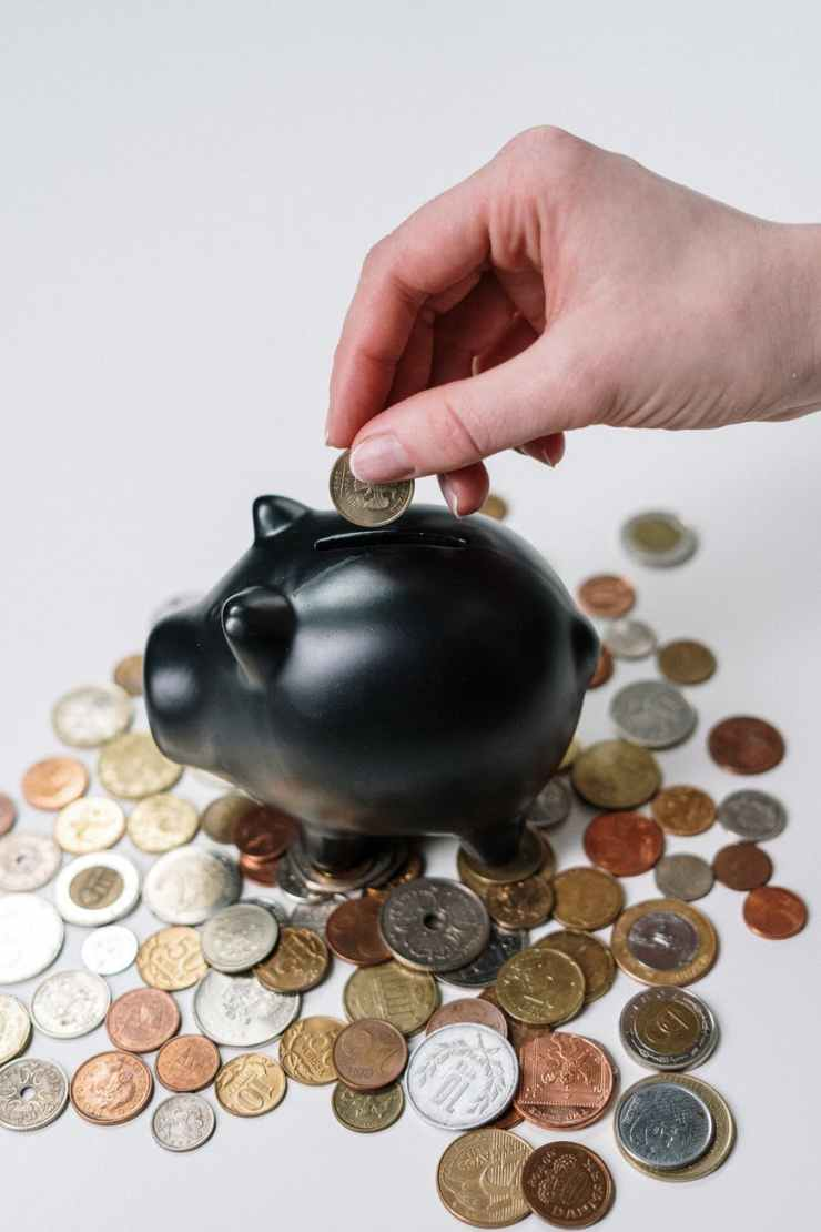 person holding black ceramic pig coin bank.  This is a post about women affording retirement.