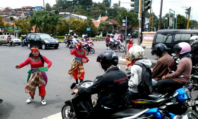 Para pegiat seni jathilan pamerken pertunjukkan di depan para pengendara motor di jalanan. Foto via Suaramerdeka