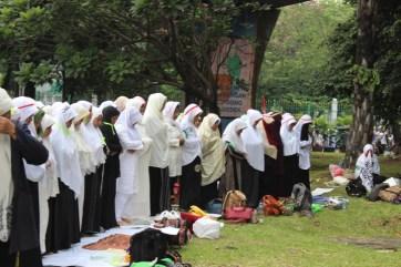 Para Peserta Wanita Aksi Massa 4 November melaksanakan shalat dhuhur berjamaah di taman monas. Foto Andika/Nusantaranews
