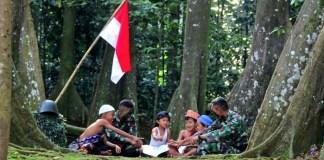 Ketika anak-anak Indonesia belajar dalam lindungan Prajurit TNI Di bawah naungan Merah Putih, (Foto: Yonif 315/Garuda)