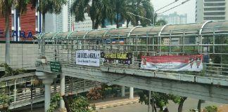 "Spanduk putih bertuliskan ""Pulangkan warga Amerika dari Indonesia"" muncul di kawasan Kemang, Jakarta Selatan dan jembatan penyeberangan orang Dukuh Atas, Jakarta Pusat. (Foto: Istimewa)"