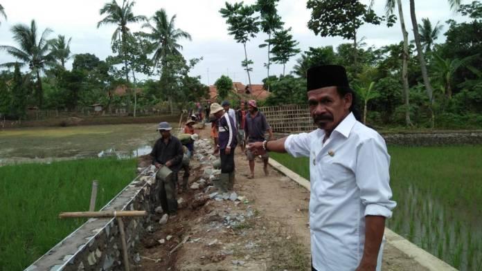 Kades Cikadu Dedy Sudjana sedang melakukan sidak lapangan mengawasi langsung pengerjaan TPT bantuan dana Desa. Foto: Fuljo/NusantaraNews