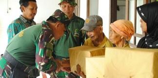 Anggota Koramil Ngetos saat menyerahkan bingkisan kepada warga masyarakat. Foto Timbul/ NusanturaNews