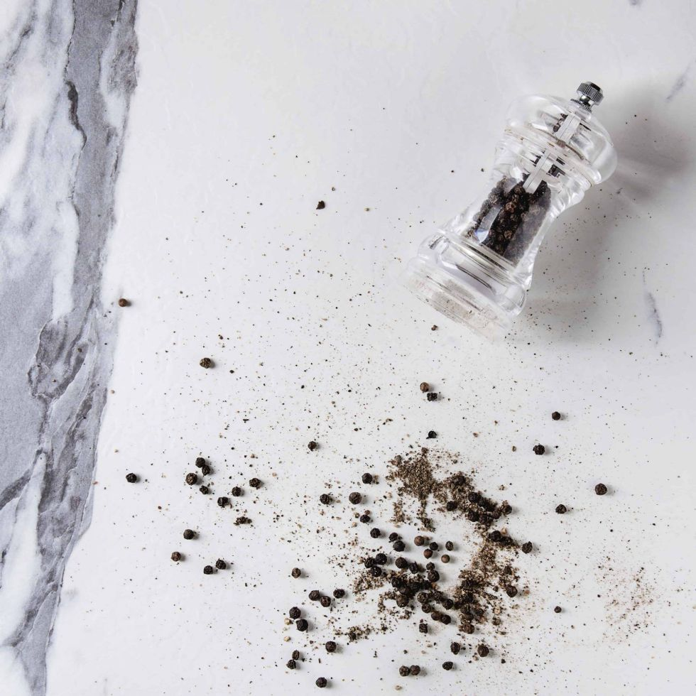 Black peppers peppercorns and ground powder from transparent pepper mill over white marble
