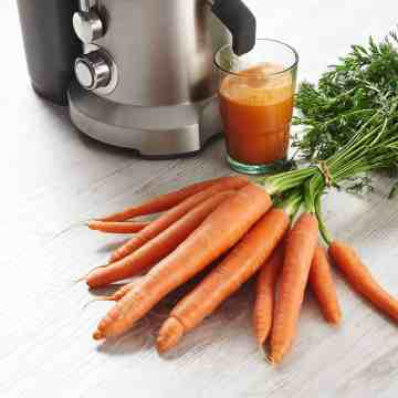 Juicer with a glass of fresh carrot juice