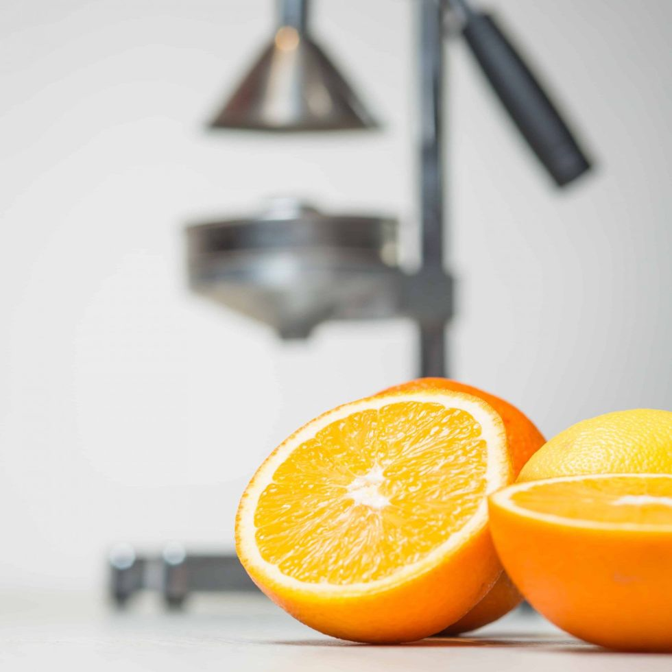 Commercial manual citrus juicer with oranges