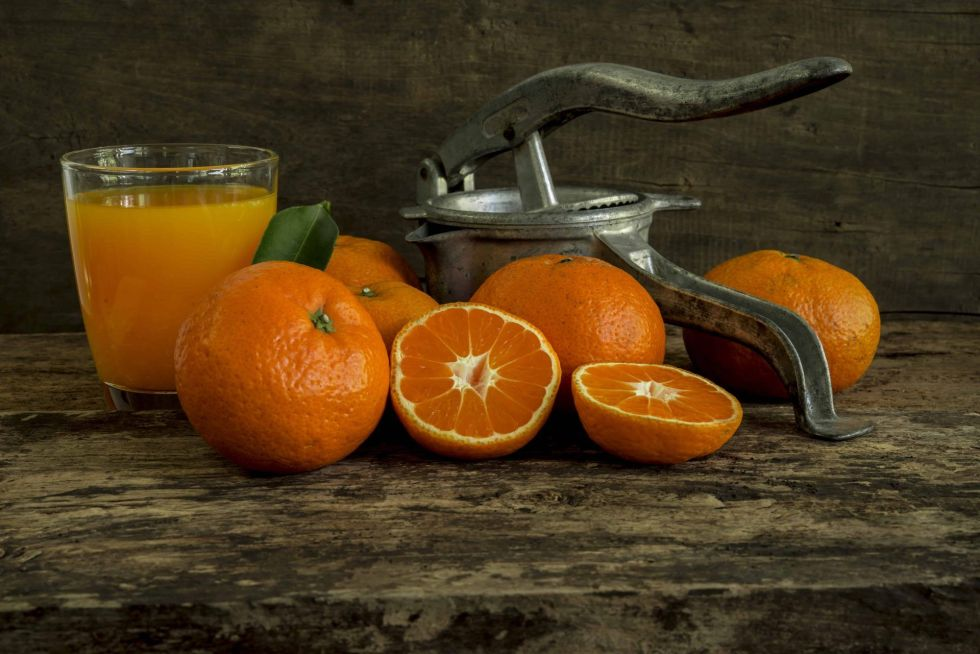 Oranges surrounding manual juicer