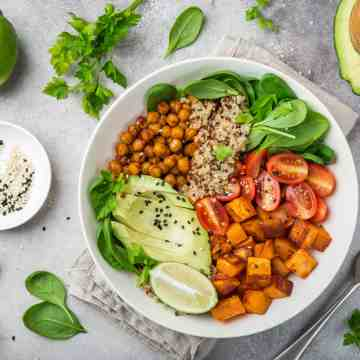 Transitioning to a plant-based diet with a healthy vegetable bowl of avocado, quinoa, sweet potato, tomato, spinach, and chickpeas