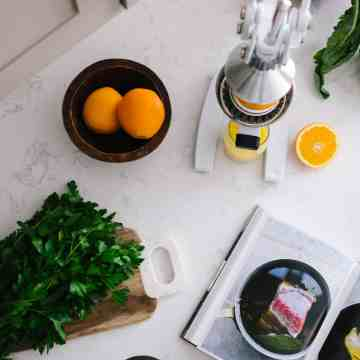 Picture of orange juicer juicing an orange next to a bowl of oranges and kale on a white countertop