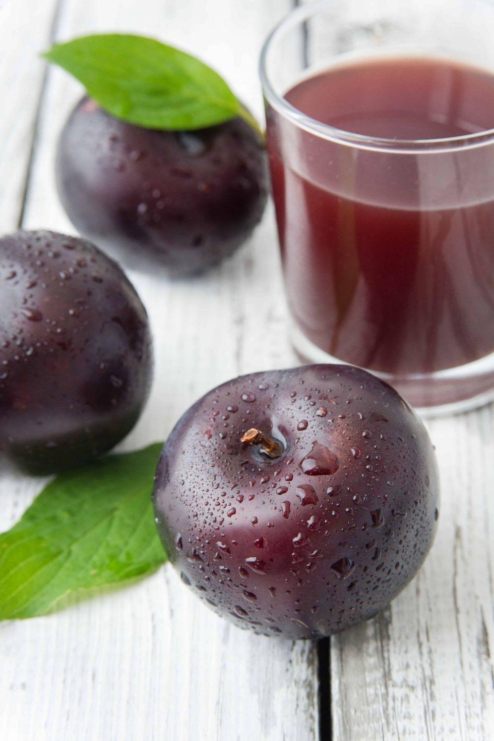 fresh plum juice on a white wood background